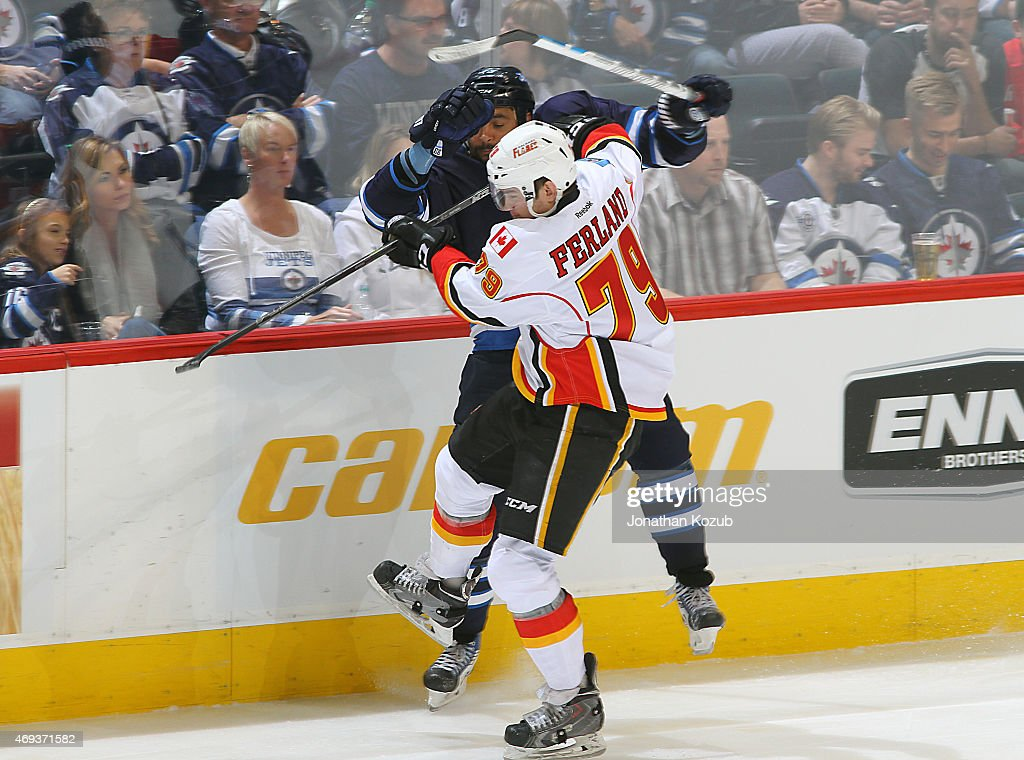 Dustin Byfuglien #33 of the Winnipeg Jets collides with Michael Ferland #79 of the Calgary Flames during third period action on April 11, 2015 at the MTS Centre in Winnipeg, Manitoba, Canada.
