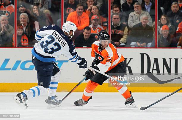 Dustin Byfuglien of the Winnipeg Jets completes a pass against Nick Schultz of the Philadelphia Flyers on January 29 2015 at the Wells Fargo Center...