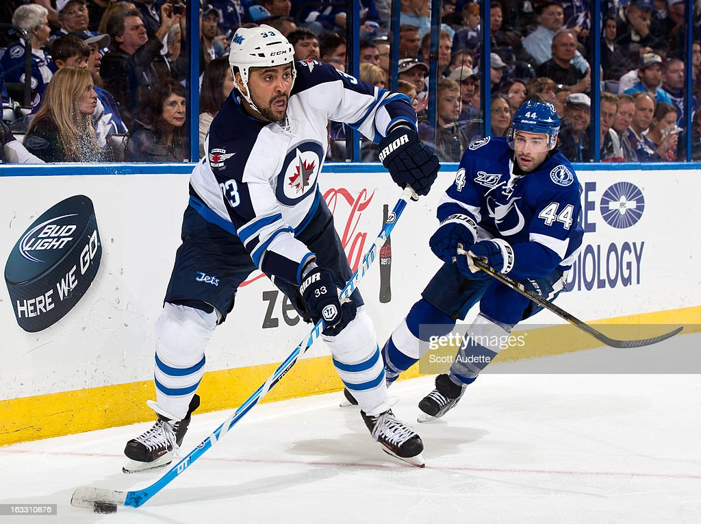 Dustin Byfuglien #33 of the Winnipeg Jets controls the puck in front of Nate Thompson #44 of the Tampa Bay Lightning during the third period of the game at the Tampa Bay Times Forum on March 7, 2013 in Tampa, Florida.
