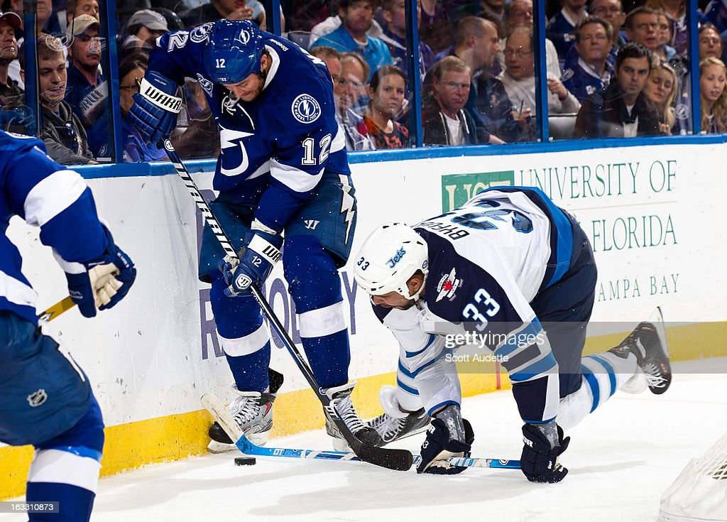Dustin Byfuglien #33 of the Winnipeg Jets fights for control of the puck with Ryan Malone #12 of the Tampa Bay Lightning during the third period of the game at the Tampa Bay Times Forum on March 7, 2013 in Tampa, Florida.