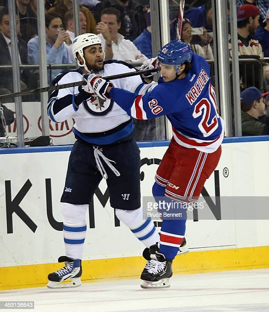 Dustin Byfuglien of the Winnipeg Jets fights off Chris Kreider of the New York Rangers during the first period at Madison Square Garden on December 2...
