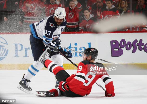 Dustin Byfuglien of the Winnipeg Jets hits Taylor Hall of the New Jersey Devils during the second period at the Prudential Center on March 8 2018 in...