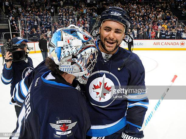 Dustin Byfuglien of the Winnipeg Jets is all smiles as he congratulates goaltender Al Montoya for backstopping the Jets to a 30 victory over the New...