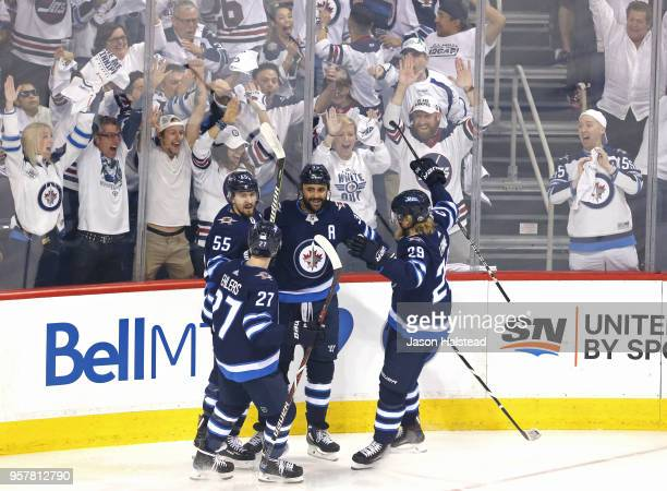 Dustin Byfuglien of the Winnipeg Jets is congratulated by his teammates after scoring a first period goal against the Vegas Golden Knights in Game...