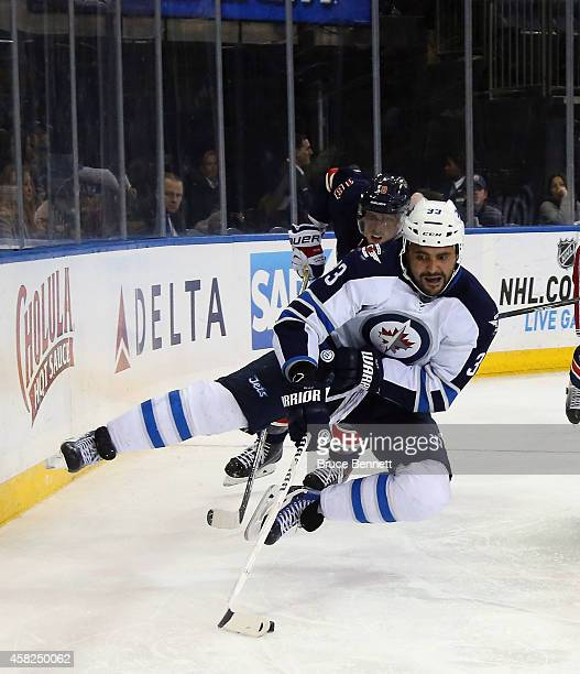 Dustin Byfuglien of the Winnipeg Jets is tripped up by Marc Staal of the New York Rangers during the third period at Madison Square Garden on...