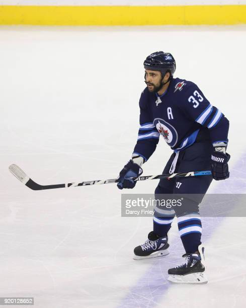 Dustin Byfuglien of the Winnipeg Jets keeps an eye on the play during first period action against the Washington Capitals at the Bell MTS Place on...