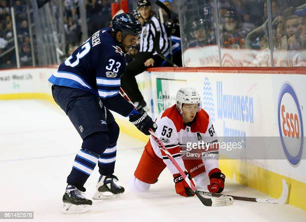 Dustin Byfuglien of the Winnipeg Jets knocks down Jeff Skinner of the Carolina Hurricanes as they battle for the puck during third period action at...