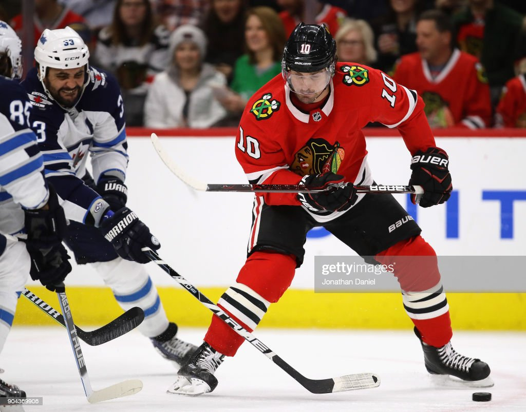 Dustin Byfuglien #33 of the Winnipeg Jets knocks the puck away from Patrick Sharp #10 of the Chicago Blackhawks at the United Center on January 12, 2018 in Chicago, Illinois. The Blackhawks defeated the Jets 2-1.