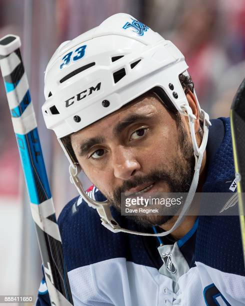 Dustin Byfuglien of the Winnipeg Jets looks down the bench during an NHL game against the Detroit Red Wings at Little Caesars Arena on December 5...