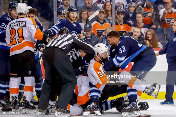 Dustin Byfuglien of the Winnipeg Jets mixes it up with Radko Gudas of the Philadelphia Flyers during a second period scrum at the Bell MTS Place on...
