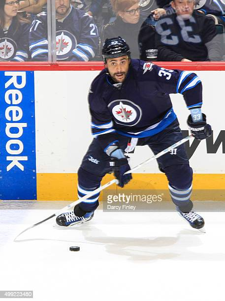 Dustin Byfuglien of the Winnipeg Jets plays the puck along the boards during secondperiod action against the Colorado Avalanche at the MTS Centre on...