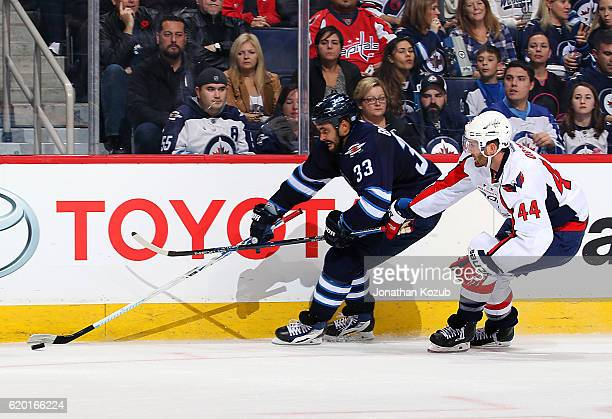 Dustin Byfuglien of the Winnipeg Jets plays the puck along the boards as Brooks Orpik of the Washington Capitals gives chase during second period...