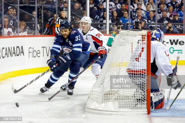 Dustin Byfuglien of the Winnipeg Jets plays the puck around the net as John Carlson of the Washington Capitals gives chase during third period action...