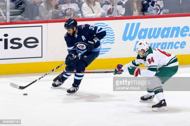 Dustin Byfuglien of the Winnipeg Jets plays the puck as Mikael Granlund of the Minnesota Wild defends during second period action in Game Two of the...