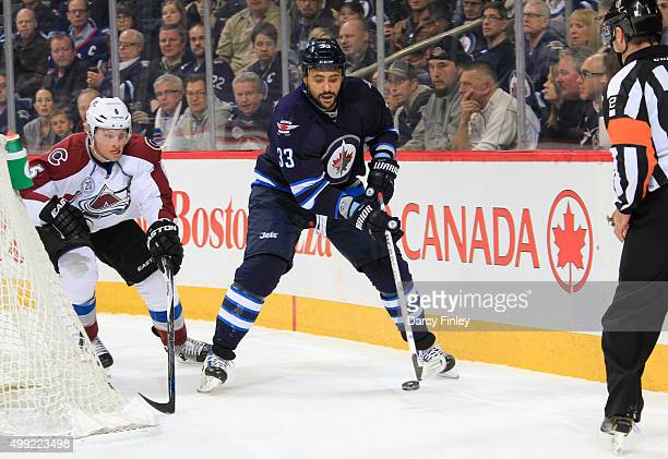 Dustin Byfuglien of the Winnipeg Jets plays the puck behind the net as Erik Johnson of the Colorado Avalanche gives chase during firstperiod action...
