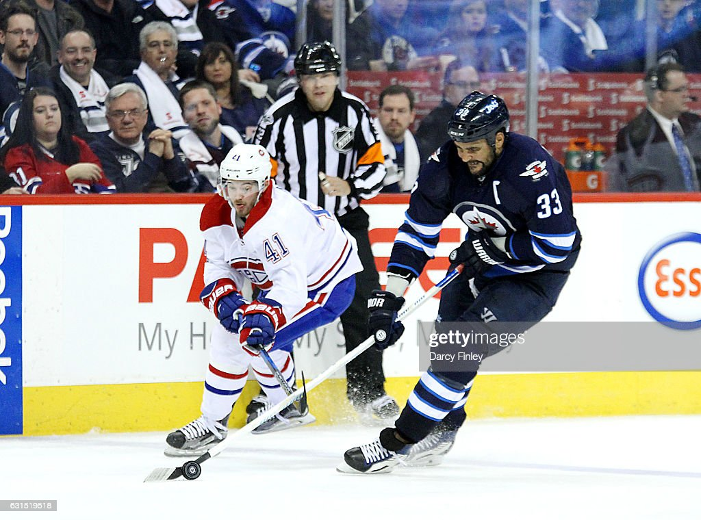 Dustin Byfuglien #33 of the Winnipeg Jets plays the puck down the ice as Paul Byron #41 of the Montreal Canadiens gives chase during third period action at the MTS Centre on January 11, 2017 in Winnipeg, Manitoba, Canada.