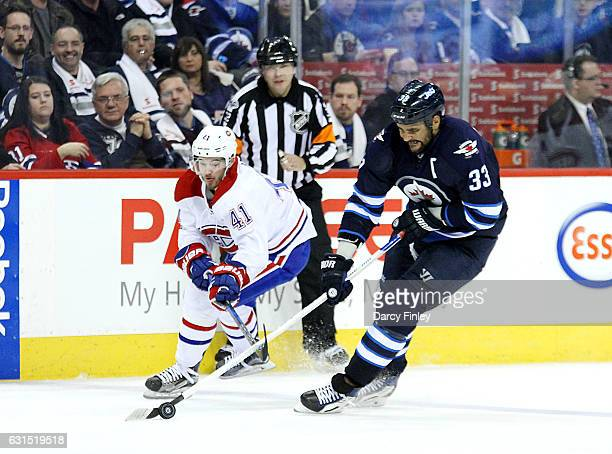 Dustin Byfuglien of the Winnipeg Jets plays the puck down the ice as Paul Byron of the Montreal Canadiens gives chase during third period action at...