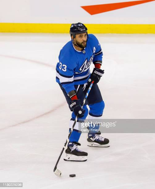 Dustin Byfuglien of the Winnipeg Jets plays the puck up the ice during second period action against the Colorado Avalanche at the Bell MTS Place on...