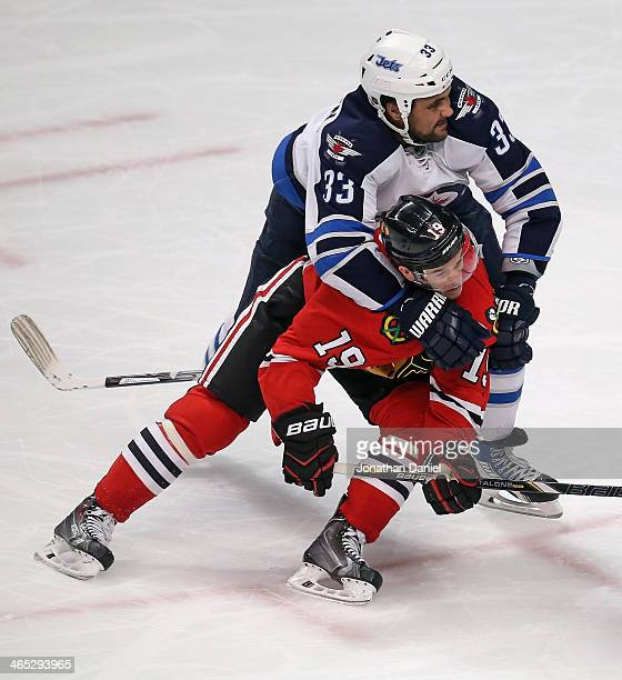 Dustin Byfuglien of the Winnipeg Jets pulls down Jonathan Toews of the Chicago Blackhawks at the United Center on January 26 2014 in Chicago Illinois