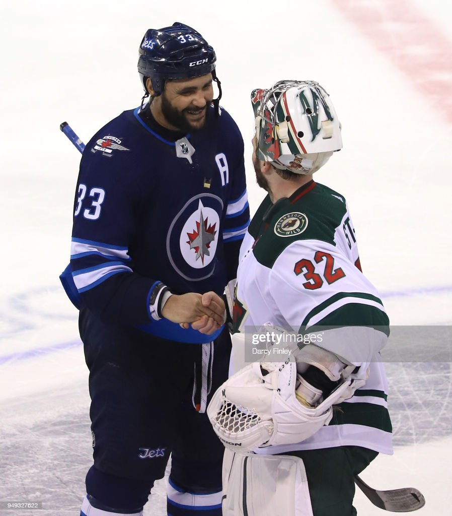 Dustin Byfuglien #33 of the Winnipeg Jets shakes hands with goaltender Alex Stalock #32 of the Minnesota Wild following a 5-0 Jets victory in Game Five of the Western Conference First Round during the 2018 NHL Stanley Cup Playoffs at the Bell MTS Place on April 20, 2018 in Winnipeg, Manitoba, Canada. The Jets win the series 4-1.