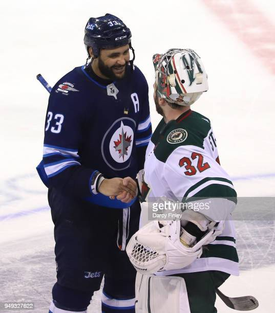 Dustin Byfuglien of the Winnipeg Jets shakes hands with goaltender Alex Stalock of the Minnesota Wild following a 50 Jets victory in Game Five of the...
