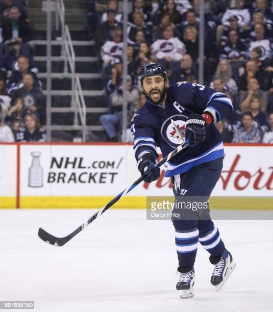 Dustin Byfuglien of the Winnipeg Jets shoots the puck down the ice during second period action against the Nashville Predators at the MTS Centre on...
