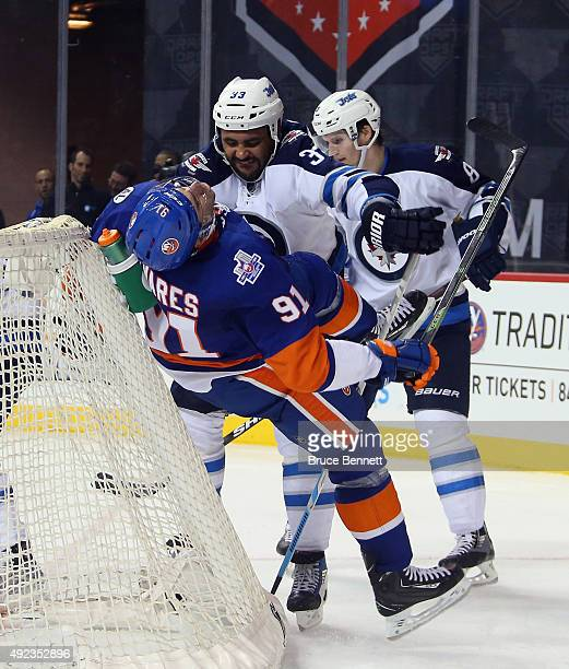 Dustin Byfuglien of the Winnipeg Jets takes a two minute penalty for roughing John Tavares of the New York Islanders during the second period at the...