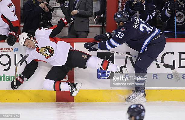 Dustin Byfuglien of the Winnipeg Jets takes down David Legwand of the Ottawa Senators in firstperiod action in an NHL game at the MTS Centre on March...