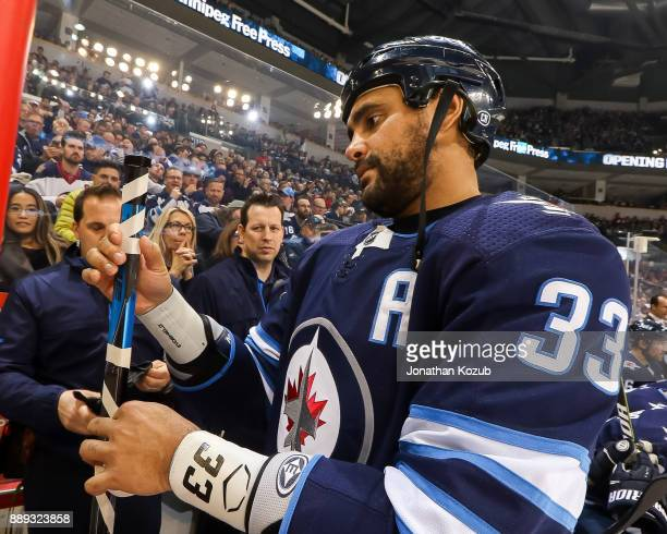 Dustin Byfuglien of the Winnipeg Jets tapes up his stick prior to puck drop for the start of the second period against the Ottawa Senators at the...