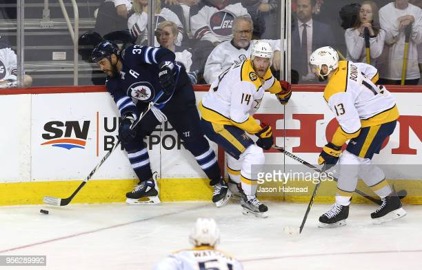 Dustin Byfuglien of the Winnipeg Jets tries to move the puck past Mattias Ekholm and Nick Bonino of the Nashville Predators in Game Six of the...