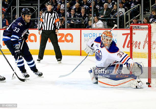Dustin Byfuglien of the Winnipeg Jets watches as goaltender Cam Talbot of the Edmonton Oilers deflects the puck just wide of the net during first...