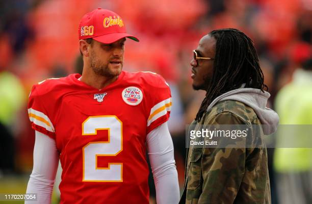 Dustin Colquitt of the Kansas City Chiefs listens to former Chiefs running back Jamaal Charles during pregame warmups prior to the game against the...