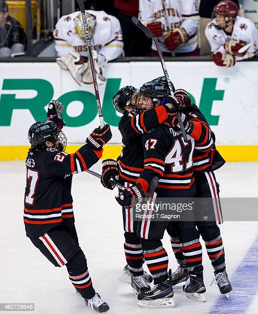 Dustin Darou of the Northeastern Huskies celebrates his game winning goal with teammate Matt Benning Dalen Hedges and Kevin Roy during NCAA hockey...