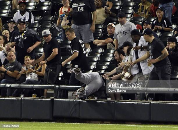 Dustin Fowler of the New York Yankees dives into the stands trying to catch a foul ball hit by Jose Abreu of the Chicago White Sox Fowler had to...