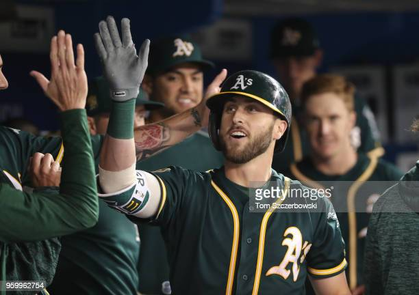 Dustin Fowler of the Oakland Athletics is congratulated by teammates in the dugout after hitting a solo home run in the third inning during MLB game...