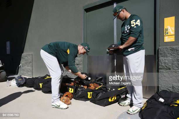 Dustin Garneau and Santiago Chavez of the Oakland Athletics check out Wilson catcher gloves prior to leaving for a game against the Cleveland Indians...
