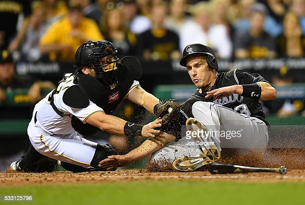 Dustin Garneau of the Colorado Rockies is tagged out at home plate by Francisco Cervelli of the Pittsburgh Pirates during the seventh inning on May...