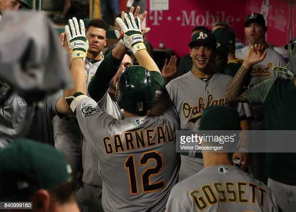 Dustin Garneau of the Oakland Athletics celebrates in the dugout with teammates after his solo homerun during the third inning of the MLB game...