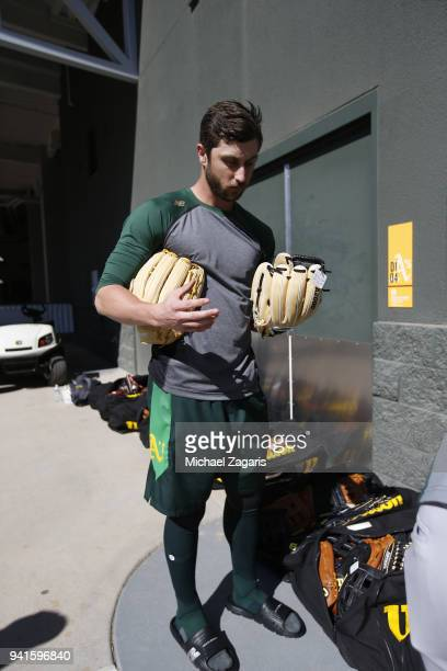 Dustin Garneau of the Oakland Athletics checks out Wilson gloves prior to leaving for a game against the Cleveland Indians at Hohokam Stadium on...