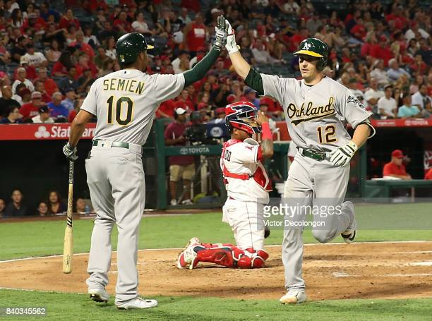 Dustin Garneau of the Oakland Athletics gets a high five from teammate Marcus Semien after Garneau scored on his solo homerun at home plate as...