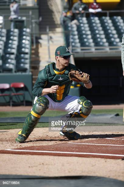 Dustin Garneau of the Oakland Athletics goes through catcher drills prior to the game against the Kansas City Royals at Hohokam Stadium on February...
