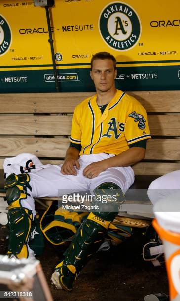 Dustin Garneau of the Oakland Athletics sits in the dugout during the game against the Seattle Mariners at the Oakland Alameda Coliseum on August 8...