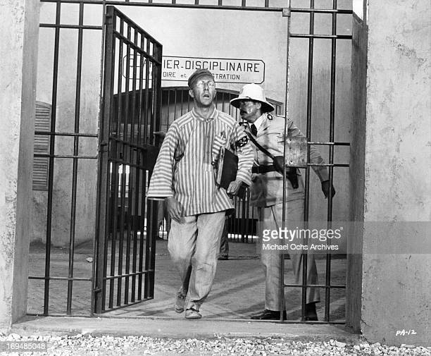 Dustin Hoffman leaves jail under guard in a scene from the film 'Papillon' 1973