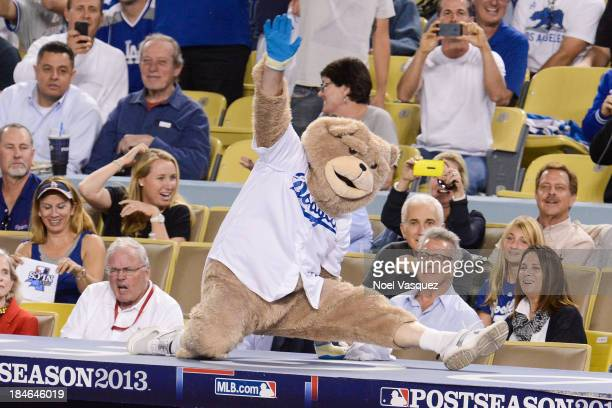 Dustin Hoffman watches an unoffical dancing bear mascot perform at Game Three of the National League Championship Series at Dodger Stadium on October...