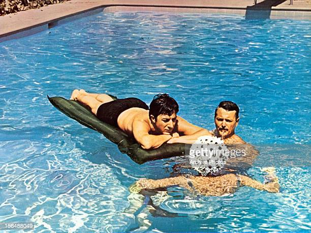 Dustin Hoffman William Daniels and Elizabeth Wilson in pool in a scene from the film 'The Graduate' 1967