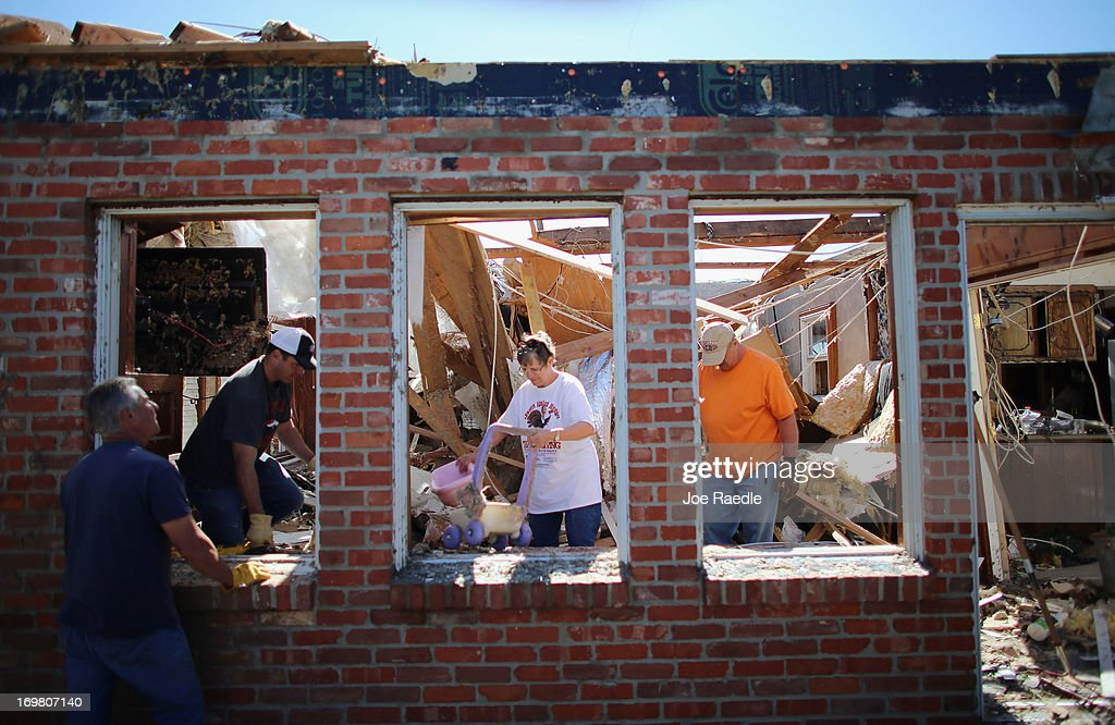 Dustin Horn (2nd L) helps his parents JoAnn Horn and Fred Horn salvage items from their home after it was damaged by a tornado on June 2, 2013 in El Reno, Oklahoma. The tornado ripped through the area friday killing at least 9 people, injuring many and destroyed homes and buildings.