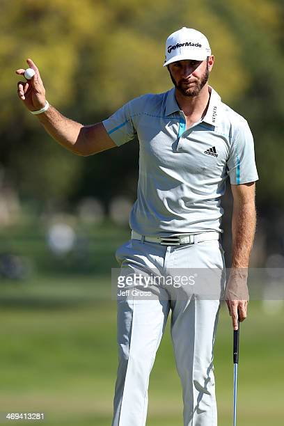 Dustin Johnson acknowledges the gallery after his birdie putt on the 2nd hole in the second round of the Northern Trust Open at the Riviera Country...