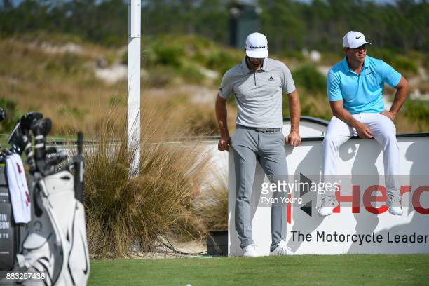 Dustin Johnson and Brooks Koepka wait to play their shots on the seventh tee during the first round of the Hero World Challenge at Albany course on...