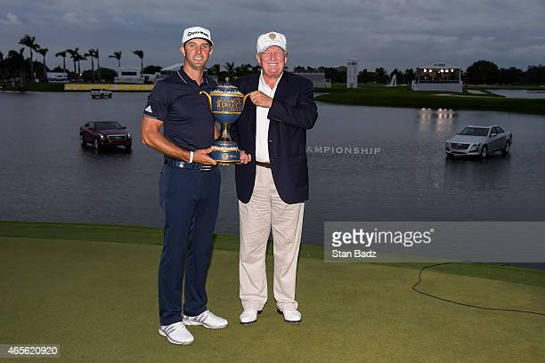 Dustin Johnson and Donald Trump hold the Gene Sarazen Cup trophy following Johnson's one stroke victory in the final round of the World Golf...