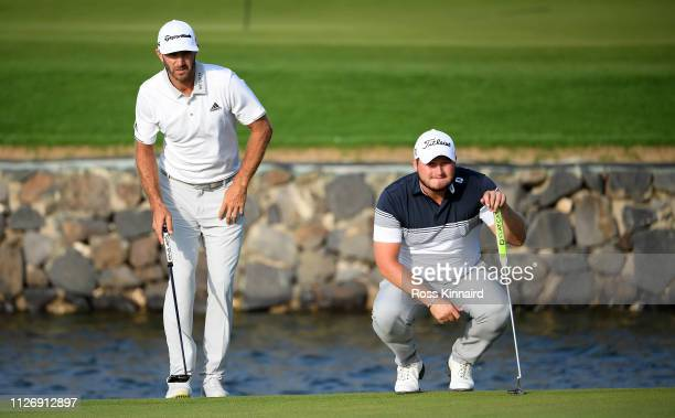 Dustin Johnson and Zander Lombard of South Africa on the par five 18th hole during the third round of the Saudi International at the Royal Greens...